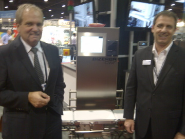 Rob Slykhuis, Pres + CEO, (left) and Rainer Dallarosa, VP Engineering, in front of Bizerba CWF checkweigher at IPPE show.