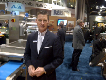 Randy Belcot of Reiser Canada at the Reiser booth in front of the Reiser RE 20. Roger Reiser in background.