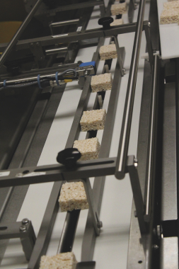 A row of freshly-made marshmallow crispy squares is fed towards the flowrapping section via a fast-moving split conveyor belt that can be easily changed by plant's personnel to accommodate fast product changeovers in minutes without any tools.
