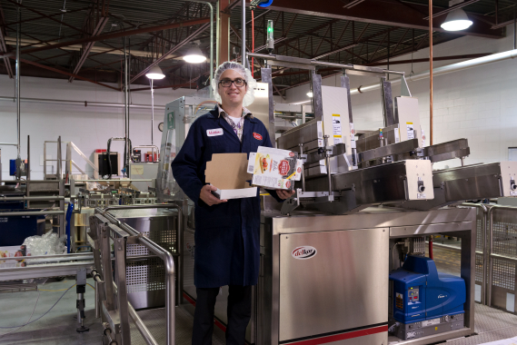 Dare Foods' Saint-Martin facility maintenance manager Matthew Beauchamp holds semi-finished boxes constructed by the high-speed Delkor Trayfecta S4 1502 carton former.