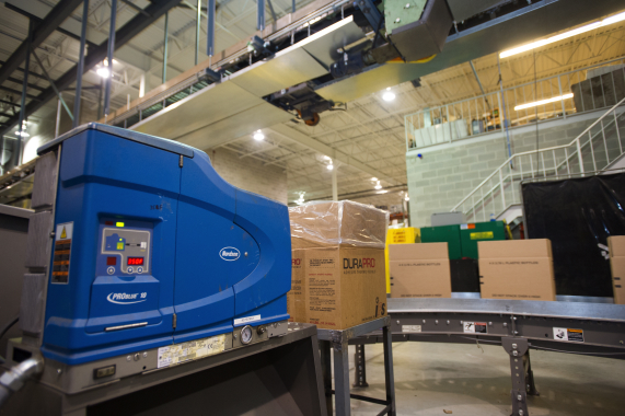 One of several Nordson ProBlue 10 hot-melt adhesive applicating systems used to seal corrugated cartons.