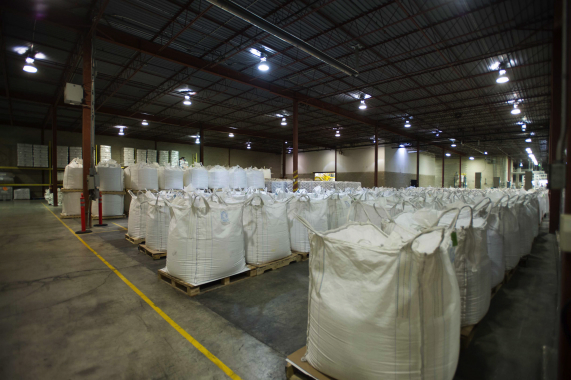 Massive batches of freshly blended and screened dishwasher powder detergent are  placed into heavy-duty woven bulk super-sacks in sequential order prior to packaging.