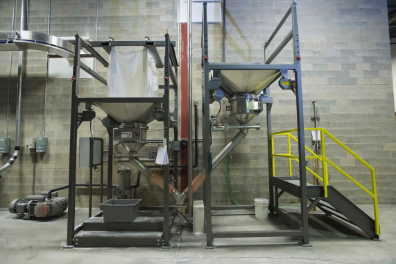 A heavy-duty bulk discharger and bucket elevators from UniTrak Corporation are used to transfer bulk powder up to the automatic weighscales on the mezzanine level above.