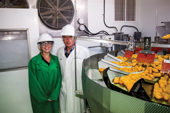 Kate Galbraith joins the Lunenburg plant's manufacturing business partner John Mills by the Ishida weighscales dispensing exact portions of fish strips and nuggets.