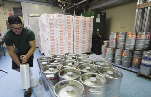A worker uses ULine stretchwrap to secure kegs supplied by MicroStar Logistics to a pallet.