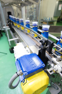 An SEW-Eurodvive motor powers a conveyor moving bottles from the heat-shrink tunnel.