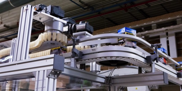 The outfeed of a wedge elevator conveyor from FlexLink quickly and safely move cartons of cigarettes to a cartoner in another part of the facility without damaging the exterior face of the brand1s packaging.