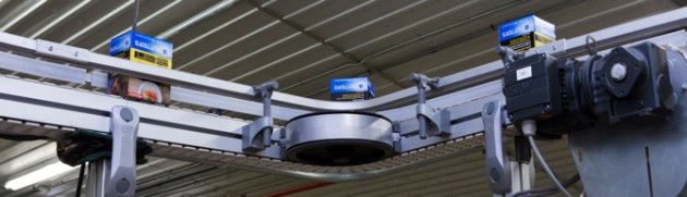 An SEW-Eurodrive motor helps provide a smooth turn for cartons of cigarettes on the elevated FlexLink conveyor line.