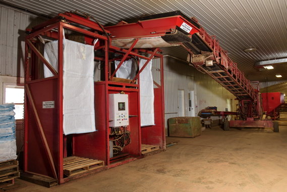 Monaghan Farms uses an automatic tote filler from Dunk River Industries to fill 3,400 pound bags in under two minutes, with an elevator lifting empty bags up to the top, and lowering them slowly as it fills to prevent product damage.