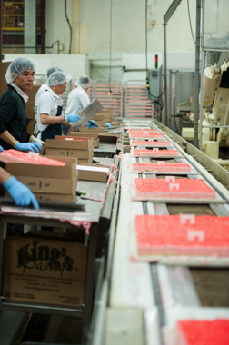 Line workers at the King's Pastry plant in Mississauga placing trays of freshly decorated pre-cut pieces of moist and delicious raspberry layered mousse cake inside the Norampac corrugated boxes used for bulk product shipments to foodservice customers.