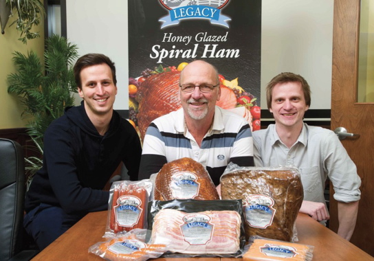 Maintaining the family tradition are (from left) Schinkel's Legacy production manager Kevin Schinkel, owner and president Tim Schinkel, and office manager Matt Schinkel, posing with some of the high-quality meat products they produce and retail at their third-generation family business in Chatham, Ont.