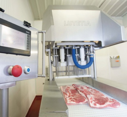 Moved via a conveyor, the whole muscle cut of raw bacon is about to receive an injection and massage of a brine solution on custom equipment built by Lutetia.