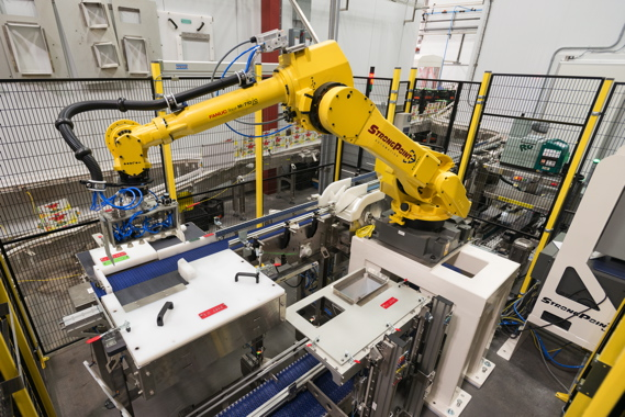 A StrongPoint Automation robotic case-packing system features a Fanuc M-710i C 50H robot outfitted with color-coded change parts.