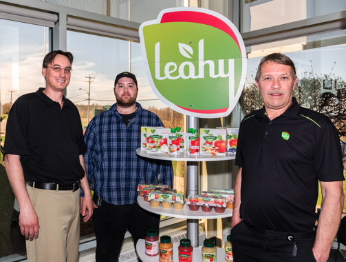 (From Left) Leahy Orchards Inc. vice-president of purchasing and logistics Philip Seguin, director of operations and supply Mitchell Leahy, and president and chief executive officer Mike Leahy with a display of Leahy brand Applesnax applesauce in a variety of packaging formats.