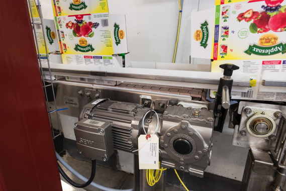 Cartons containing pouches of Leahy Orchards' Applesnax brand of applesauce move along a Storcan manufactured conveyor system powered by an SEW-Eurodrive motor.
