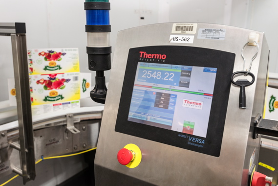 A Thermo Scientific Ramsey VERSA checkweigher quickly checks and verifies the weight of full cases of Applesnax applesauce before closing the flaps to ensure each contains the pre-determined number of product packs.