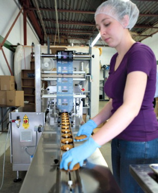 A machine operator manually places freshly-baked cookies onto the infeed conveyor track of the new Sleek 50 Wrapper flowwrapping machine manufactured by Paxiom.