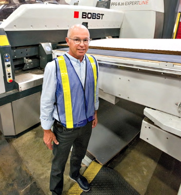 Mitchel-Lincoln Packaging president Jimmy Garfinkle strikes a pose at the feed end of the 8.20 EXPERTLINE flexo folder-gluer installed last year at the company's St-Laurent facility.
