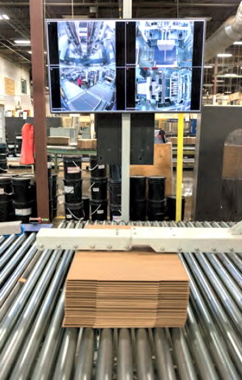 Large video monitors provide end-of-line operators at the Mitchel-Lincoln facility in St-Laurent with unobstructed views of all the process stages taking place in the forming and transferring of large stacks of corrugated boxes towards the plant's shipping area. (Also see below)