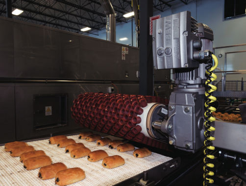 An SEW-Eurodrive motor powers a rubber head roller that gently transports the freshly-made baked goods from the oven line down onto a cooling line.