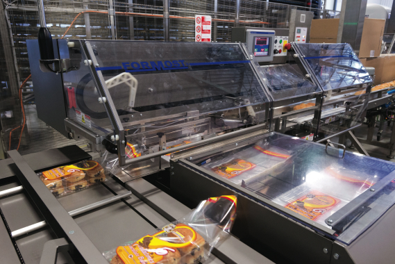 Baked goodies inside a plastic tray are moved through a pair of Formost Fuji horizontal baggers that quickly open up individual plastic bags to allow the trays to enter before sending them on its way to be individually clip-sealed.