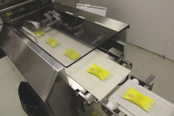 Foil-wrapped marshmallow crispy squares exiting the Pack 401 machine's discharge section at high speeds.