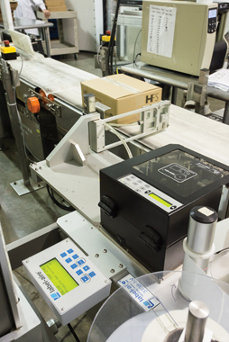 A custom-manufactured Label-Aire application system purchased via Ahearn & Soper prints and applies labels with fully-detailed product data onto shipping cartons.