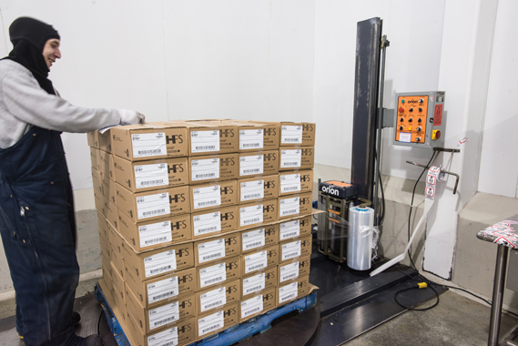 A HFS employee carefully prepares a pallet load of packaged food items on an end-of-line automatic stretchwrapper, manufactured by Orion Packaging Systems, to prevent product shifting during transport to healthcare facilities across Canada.