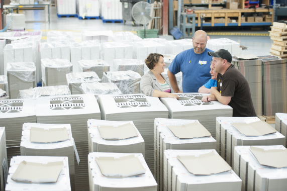 Ingersoll Paper Box president Sarah Skinner (left) chats with employees amongst rows of completed print jobs.