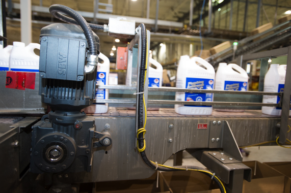 An SEW-Eurodrive motor helps smoothly propel a conveyor line carrying large plastic containers of plumbing antifreeze to the line's cartoner.