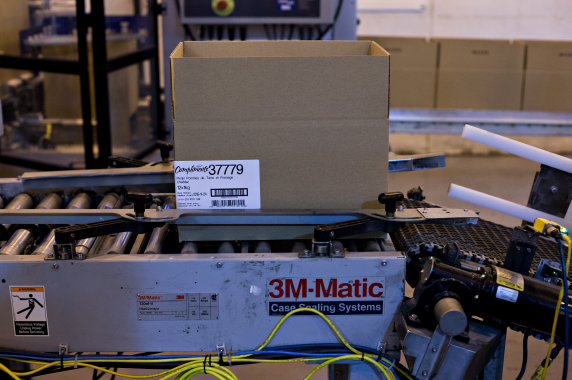 After traveling via a conveyor powered by a Baldor Electric AC motor, a case of perogies heads to the model 3M-Matic case-sealing system manufactured by the 3M Company.