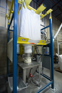 A heavy-duty woven super sack filled with bulk powder detergent blend is prepped up for discharge and processing into monodose, single-use dishwashing detergent tablets.
