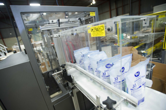 Precise quantities of filled stand-up pouches of dishwasher detergent pods making their way out of the fully-automatic collator manufactured by Eagle Packaging Machinery.
