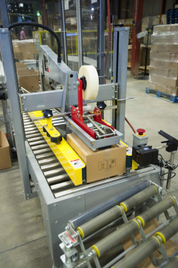 An automatic case-sealing machine from Eagle Packaging Machinery applies strips of high-strength sealing tape onto the top of each passing corrugated box.
