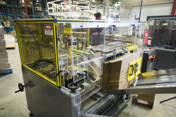 Stacks of corrugated carton blanks being loaded into the magazine of the high-speed, automatic Boxxer T-12 case-erecting machine manufactured by Eagle Packaging.