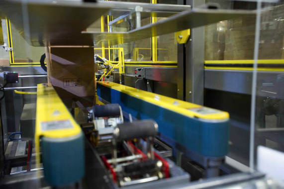 A close-up view of the Eagle Packaging Machinery's case-erector feeding the JemPak packaging lines with corrugated shipping boxes made by Atlantic Packaging Products.