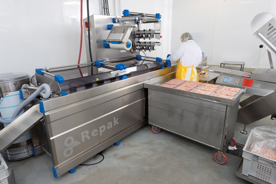 An Edelweiss employee placing pre-weighed portions of veal bacon by hand into a bottom pocket of film on the Reiser Repak RE15 form/fill/seal thermoforming machine.