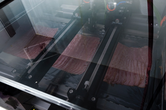 A close-up view of veal bacon slices entering the Reiser Repak RE15 thermoformer for final sealing.