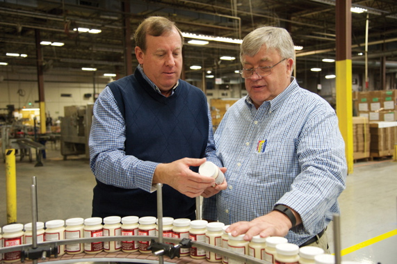 Plaid Enterprises chief operating officer John Michalek (left) and plant director Norman Thomas examine filled arts and crafts paint bottles being conveyed to the high-performance LabelStar System 3 top cap labeling unit.