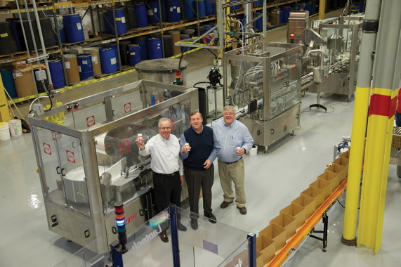 (From left): Plaid Enterprises, Inc. chief executive officer and president Mike McCooey; chief financial officer and chief operating officer John Michalek; and plant director Norman Thomas find good cheer with the turnkey Capmatic filling and capping line installed at the company's 270,000-square-foot production facility in Decatur, GA.