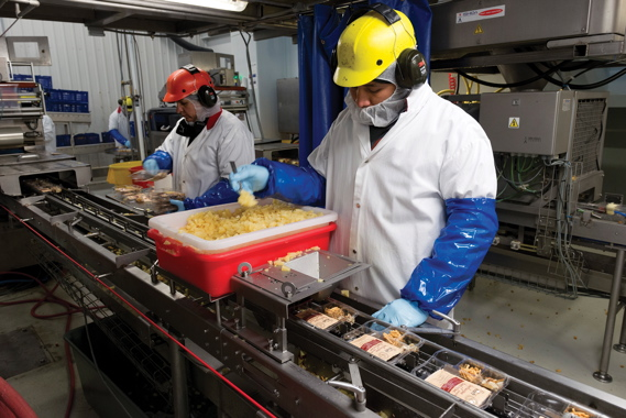 Workers inside the plant's kit assembly room wear full protective clothing to ensure a highly sanitary work environment to comply with strict food safety standards.