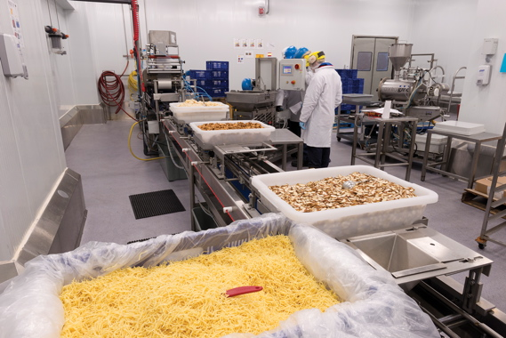 Totes filled with noodles, nuts, veggies and other key fresh ingredients used in production of the recently-launched Fresh Attitude Asian Stir Fry kits make their way inside the Serrington plant's ultra-clean kit assembly room for high-precision portioning and filling.