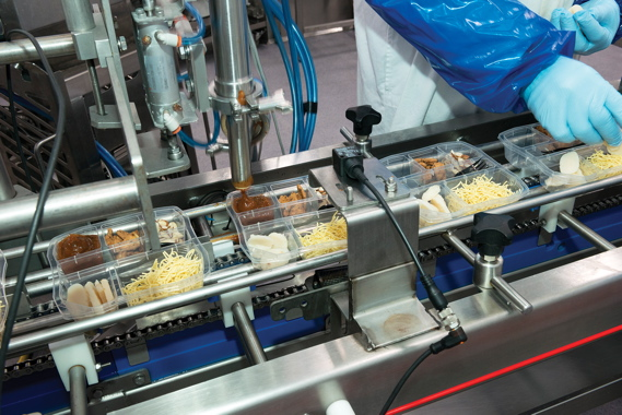 The high-precision ControlGMC piston-filler dispenses toppings and sauces into the multicomparment plastic trays inserted inside the microwavable plastic bowls used to package the new Fresh Attitude Asian Stir Fry kits, both developed by IMS Plastics.