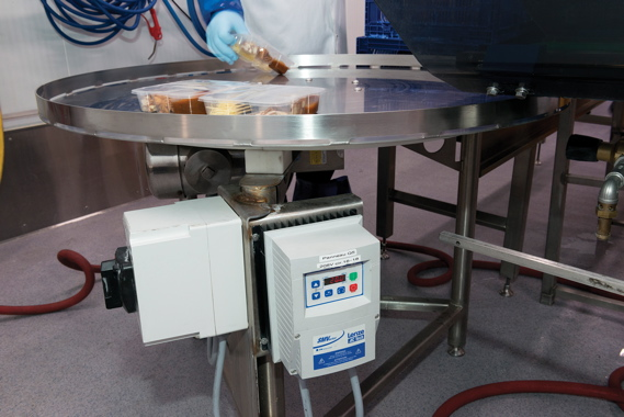 A Lenze decentralized inverter drive SMV IP65 (foreground) is used to ensure highly precise movement of the circular conveyor being loaded with freshly-filled multicompartment plastic trays that hold all the toppings and sauces used in the Asian Stir Fry kits.