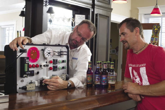 Using a demonstration box, Omron account manager Ralph Nymann discusses with Flying Monkeys automation specialist Chris Mavreas the basics of how an industrial control system can further increase the craft brewery's production consistency.