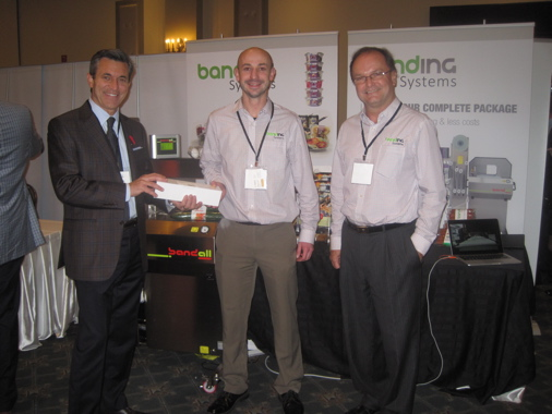 (From left) Canadian Packaging senior publisher Stephen Dean congratulates Bandall Systems Dariusz Chmielinski and Paul Slipper for the Bandall technology being chosen the most interesting and innovative technology at the 2015 Top 50 Packaging Ideas Expo.