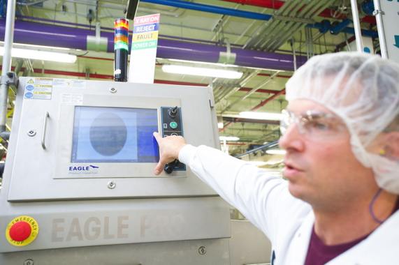 Galen Sienicki points out some the of powerful capabilities, including inline checkweighing, offered by the recently-installed Pro Eagle X-Ray inspection system, supplied by PLAN Automation, on one of the plant's margarine packaging lines.