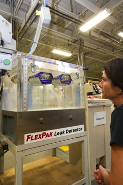 Tempo Plastics pouch operator Mona Russell testing stand-up pouches for leaks—randomly plucked from the production line. If no bubbles are present in the tank, the pouches pass the quality assurance check.