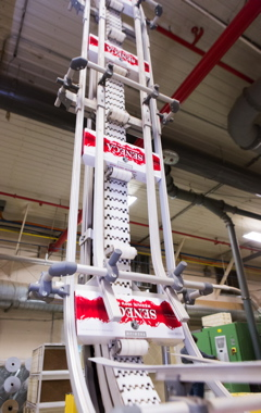 A front view of a cleated Flexlink elevator conveyor moving cartons of cigarettes up to an elevated line.