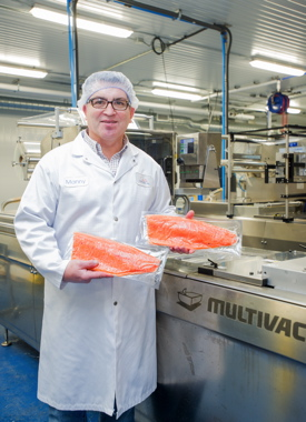 John O's Foods vice-president of operations Manny Resendes holding up two packs of ruby-red trout sealed via the company's recently-purchased model R 105 thermoforming machine supplied by Multivac Canada.